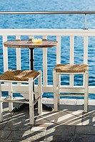 Empty table with stools near a railing in a restaurant, Mykonos, Cyclades Islands, Greece