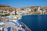 High angle view of tourists resting on lounge chairs on the deck of a ship, Skala, Patmos, Dodecanese Islands, Greece