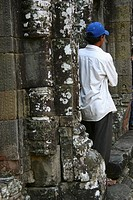Rear view of a mid adult man leaning against a wall, Ta Prohm Temple, Angkor Wat, Siem Reap, Cambodia