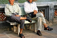 Two mature men sitting on a bench, Hanoi, Vietnam