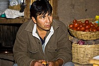 Close-up of a mature man sitting at a market stall, San Juan de Chuccho, Peru