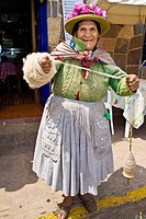 Portrait of a senior woman standing and holding a spool of thread, Peru