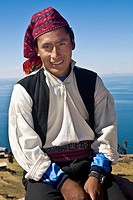 Portrait of a young man sitting and smiling, Taquile Island, Lake Titicaca, Puno, Peru
