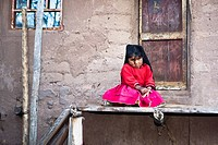 Portrait of a girl sitting in front of the gate of a house, Taquile Island, Lake Titicaca, Puno, Peru