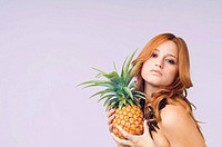 Portrait of a young woman holding a pineapple