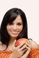 Portrait of a young woman holding a mango and smiling