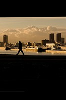 Silhouette of man walking along the Maas River, Rotterdam, the Netherlands