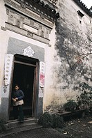 Mature woman standing at doorway, ancient common people residence of Ming and Qing dynasty, Lu Village, Yi County, Anhui Province of People's Republic...