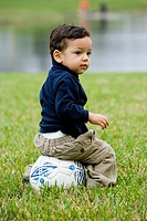 Boy sitting on a soccer ball