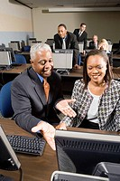 Older man helping younger business colleague in computer lab
