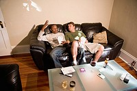 Two young men, a gay couple, relaxing on a sofa