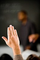 Close_up of a raised hand in class