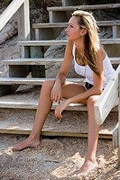 View of a young woman sitting on stairs at the beach looking away