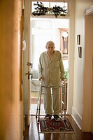 Feeble senior man walking down hallway using walker