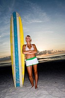 Surfer girl posing on beach with surfboard