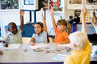 Children raising hands in art class