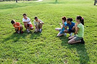 Three boys sitting opposite three girls on grass at a park