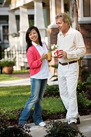 Affectionate mature inter_racial couple holding coffee mugs in front of their house