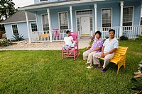 Pregnant woman and her parents seated in front lawn of house