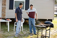 Two men preparing a cookout in front of trailer home