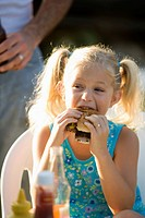 Young girl eating a burger