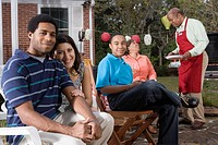 Interracial couple and family enjoying backyard barbeque