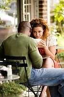 Close_up view of young couple sitting at a table at a sidewalk cafi