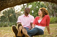 Close_up of smiling young multi_ethnic couple sitting on grass outdoors