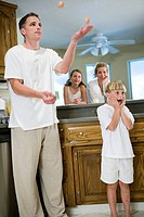 Father juggling eggs with family in kitchen