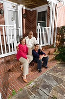 Portrait of mature couple and their son sitting on front porch of house