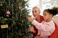 Mother with daughter in pajamas decorating Christmas tree