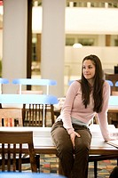 Smiling young woman sitting on a desk in the reading room of a library