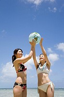 Two young women playing with balloon in form of Earth in front of sea