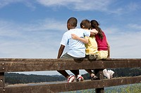 Three children 8-12 years sitting on fence by lake, rear view