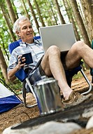Mature man using laptop in camp site
