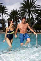 Couple leaving swimming pool, laughing