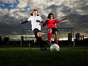 Two female football players 10-11 running after ball on pitch