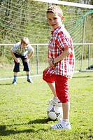 Two boys 8-9 playing soccer, one waiting in goal, portrait