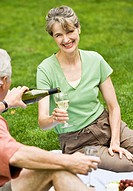 Mature man pouring wine for mature woman at picnic in field