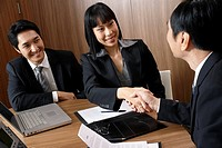 Business people shaking hands over table in conference room