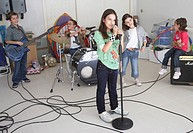 Group of children 7-10 in band, playing instruments in garage