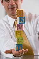 Businessman with blocks spelling INVEST