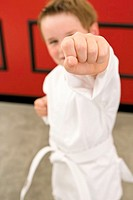 Boy 4-5 years doing karate punch, focus on hand