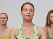 Three mature women, performing yoga, eyes closed