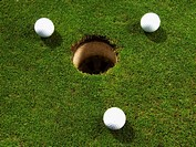 Three golf balls near hole, close-up