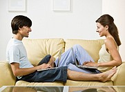 Young couple using laptops on couch
