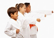 Three children 7-9 in judo position, studio shot, profile