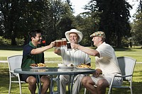 Three men toasting with beer, sitting at outdoor table