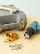Power drill, hammer, tape measure, nails and toolbox on table, close-up