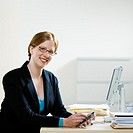 Young businesswoman working on PDA at desk